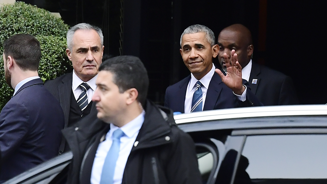 Former US President Barrack Obama (C) waves as he leaves the hotel, in central Paris, on December 2, 2017 before appearing as a guest of honour at an innovative communications conference organised by Les Napoleons group.  Martin BUREAU / AFP