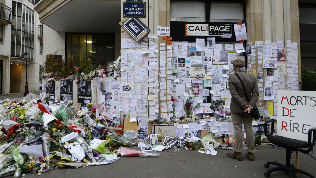 This file photo taken on January 12, 2015 shows people visiting a makeshift memorial near the headquarters of the French satirical weekly Charlie Hebdo in Paris in tribute to the 17 victims of a three-day killing spree by homegrown Islamists.