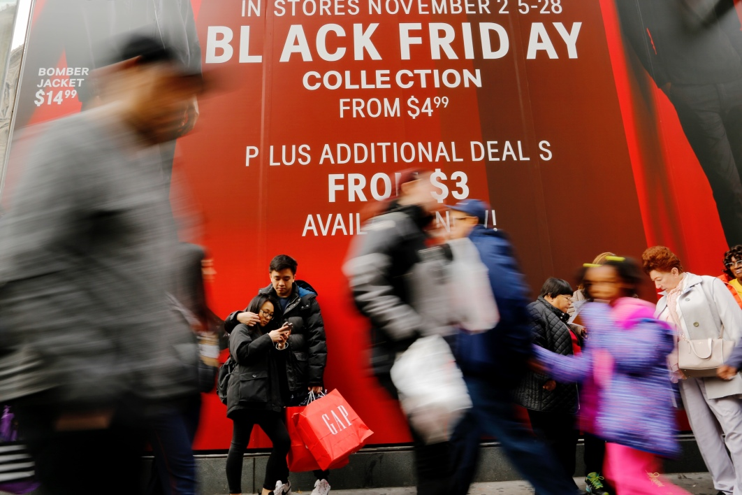 NEW YORK, NY - NOVEMBER 25: Shoppers walk next to retail stores during Black Friday events on November 25, 2016 in New York City.