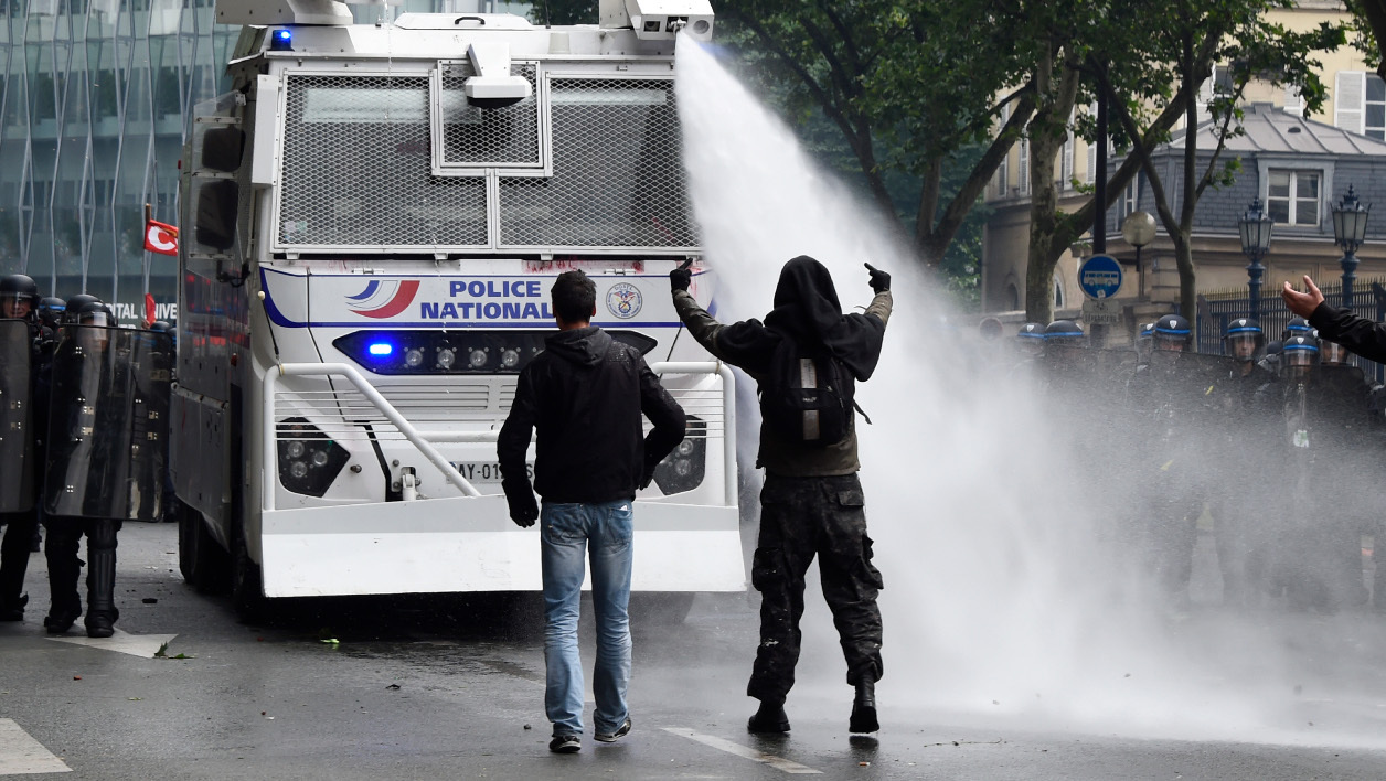 canon à eau French anti-riot police officers spray water from a vehicle to protesters gesturing during a demonstration against proposed labour reforms in Paris on June 14, 2016. Several hundred masked protesters hurled objects at police on June 14 during a demonstration in Paris against a contested reform of French labour laws, authorities said.  DOMINIQUE FAGET / AFP