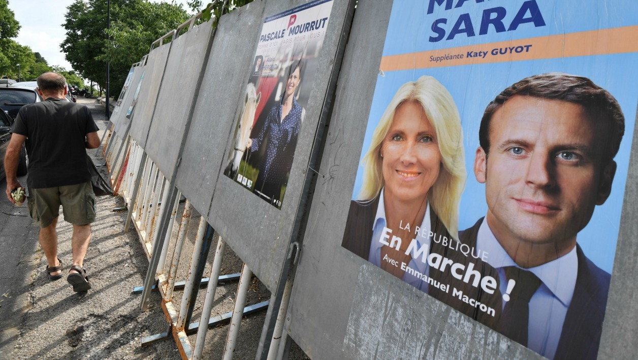 A woman walks past an electoral poster of La Republique en marche (REM) party's candidate Marie Sara on May 30, 2017, in Saint Gilles, southern France, ahead of the upcoming French legislative elections.  PASCAL GUYOT / AFP