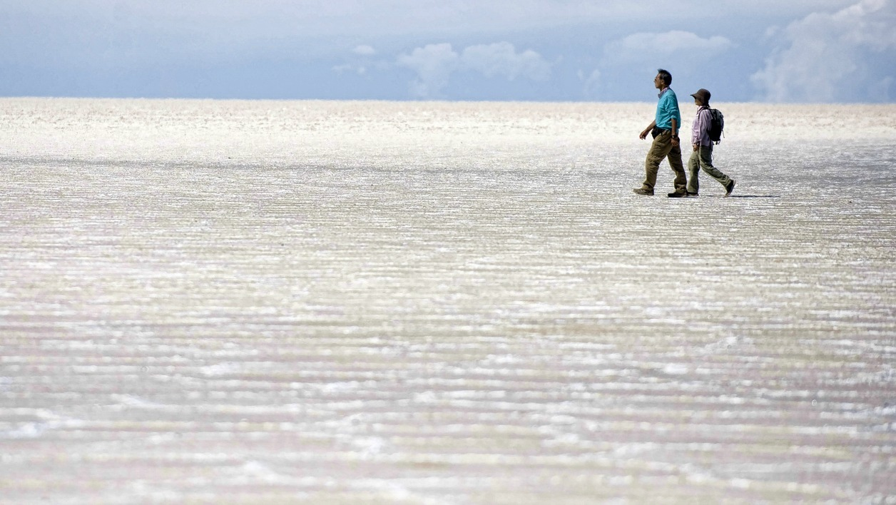 Tourists are seen walking along the salt flats at the Uyuni salt flats, Bolivia on October 6, 2009. The Uyuni salt flats are estimated to contain 10 billion tons of salt - of which 25,000 tons are extracted every year - as well as 100 million tons of lithium
