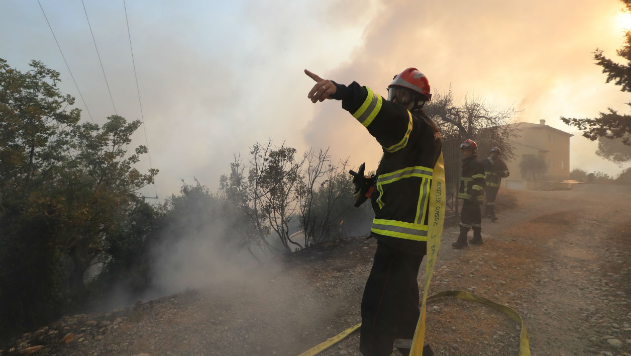 A firefighter points towards a direction as firefighters fight against a fire in Castagniers, near Nice, on July 17, 2017.  Valery HACHE / AFP