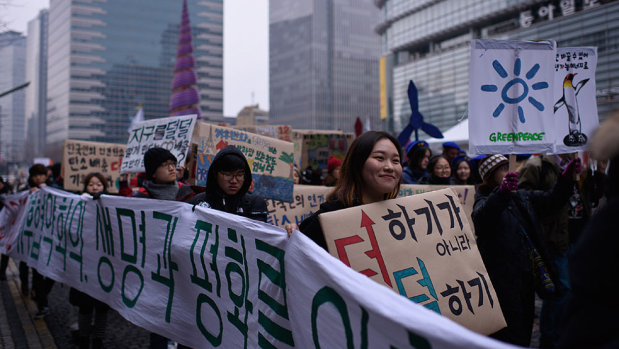 Environmental campaigners hold placards as they march in Seoul on November 29, 2015. Environmentalists were marching as part of a weekend of events across the globe demanding results from next week's historic COP21 summit in Paris.
