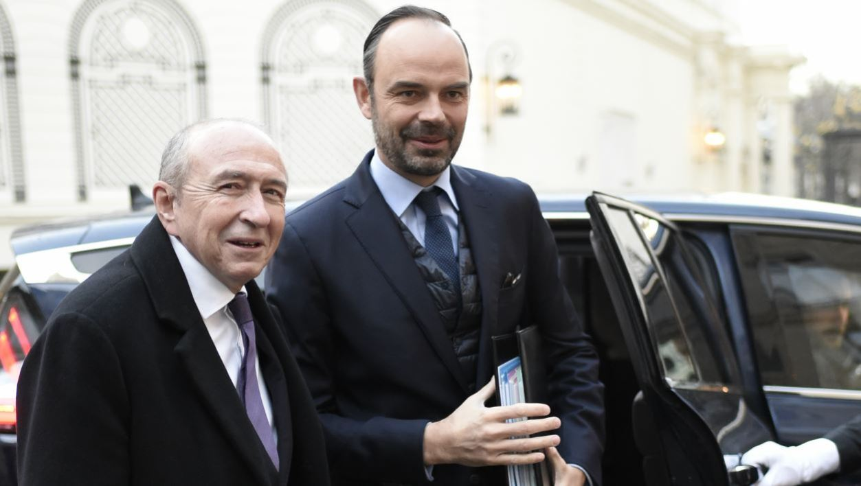 French Interior Minister Gerard Collomb (L) greets French Prime Minister Edouard Philippe as he arrives to attend a government's New Year breakfast meeting at the Interior Ministry in Paris on January 3, 2018.