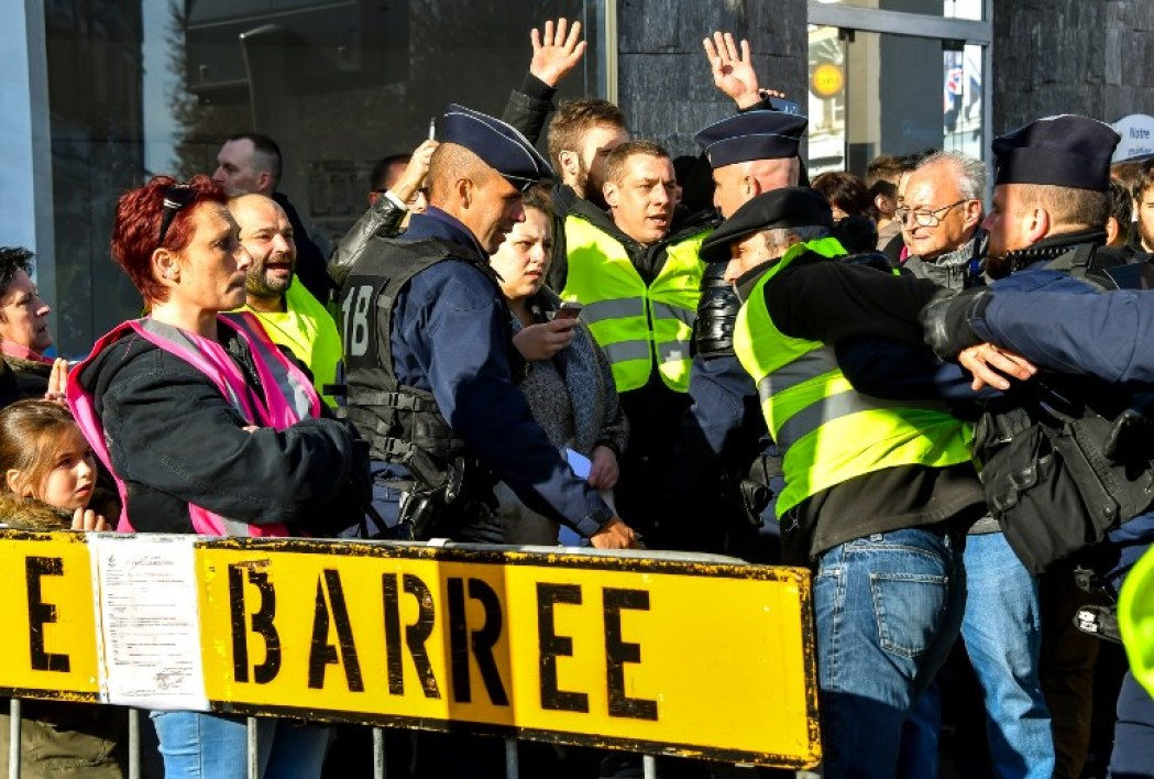 """Anti-riot policemen evacuate protesters wearing yellow jackets (""""gilets jaunes"""") during a protest against the rising of the fuel and oil prices on November 9, 2018 near the town hall of Albert, northern France, ahead of a visit of tyhe French president and the Britain Prime minister during the 100 anniversary of the WWI armistice celebrations. The yellow vest is the symbol of the French drivers protesting against the rising of the fuel and oil prices. PHILIPPE HUGUEN / AFP"""