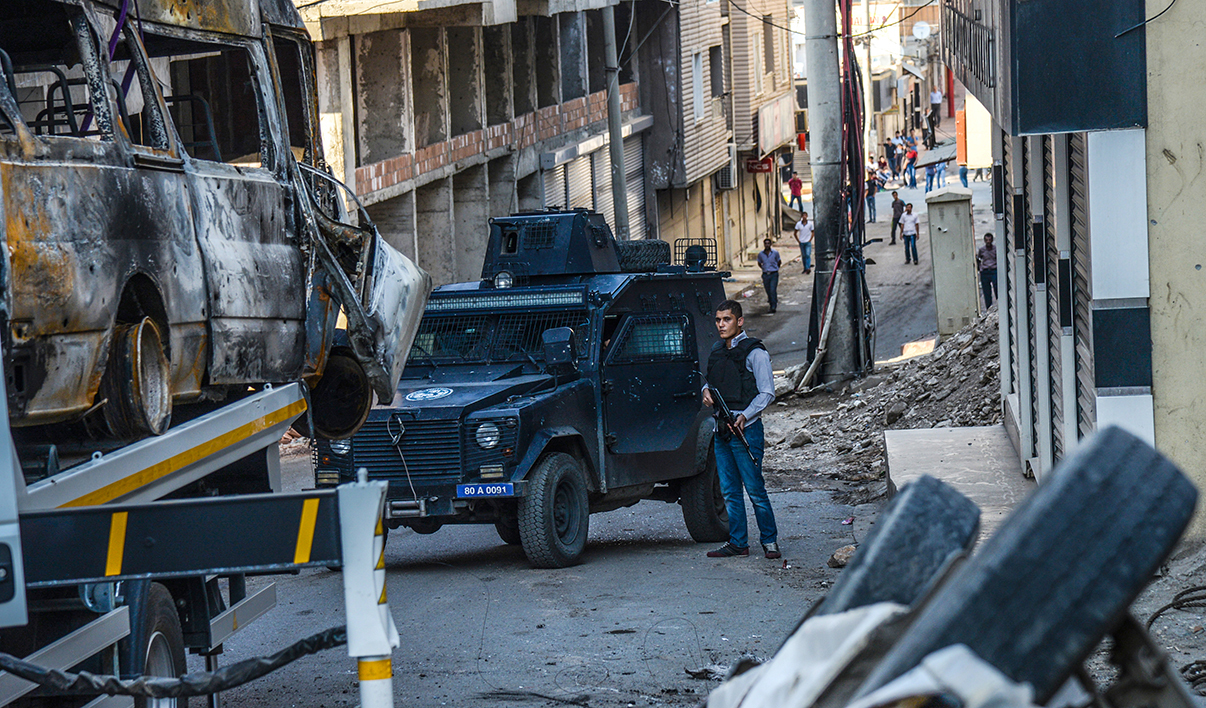 A picture taken on October 5, 2015 shows destroyed vehicles as a Turkish police officer guards a street in Silvan, after clashes between Turkish army and Kurdish rebels. Turkish authorities on September 2, imposed a curfew in the mainly Kurdish southeastern town of Silvan, saying 17 suspected Kurdish militants had already been killed hours after the military lockdown was enforced.