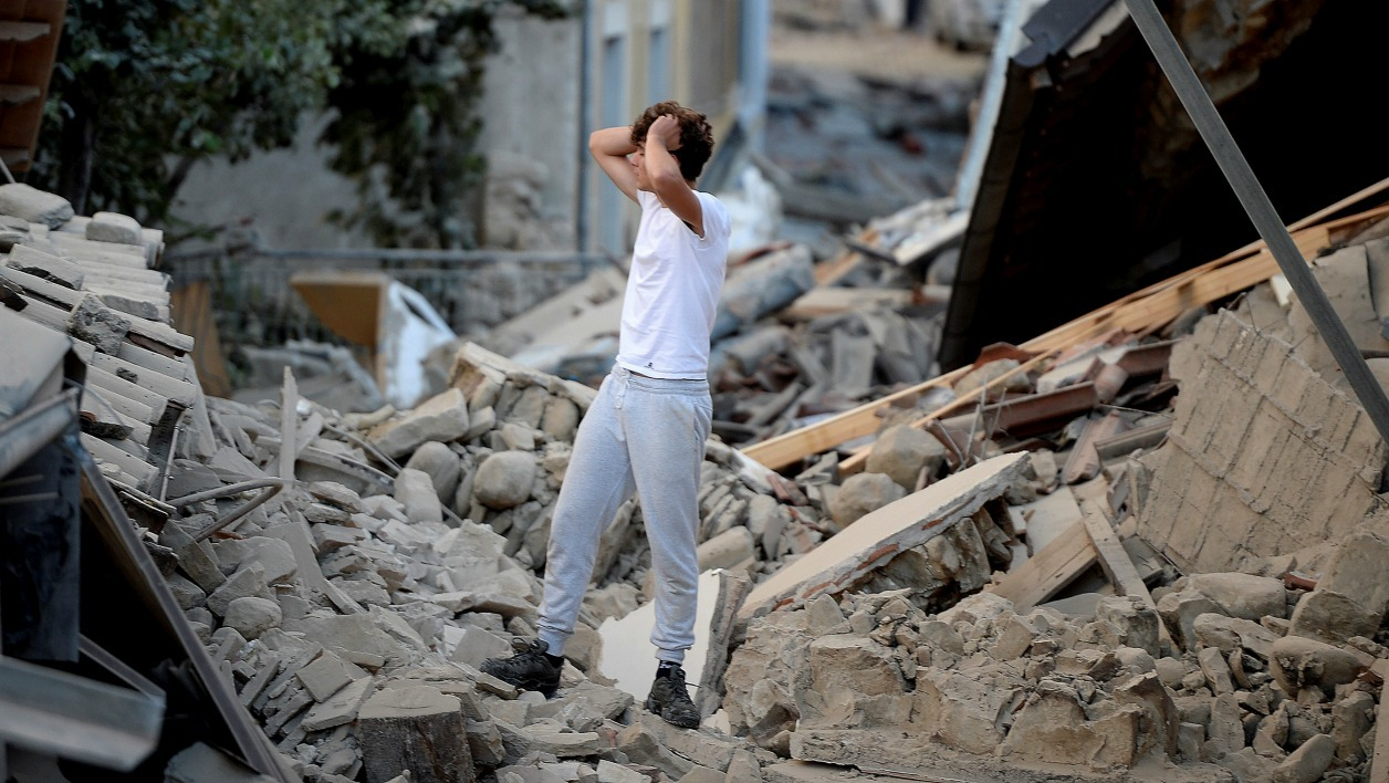 A man stands among damaged buildings after a strong earthquake hit central Italy, in Amatrice on August 24, 2016. A powerful 6.2-magnitude earthquake devastated mountain villages in central Italy on August 24, 2016, left 38 people dead and the total is likely to rise, the country's civil protection unit said in the first official death toll.