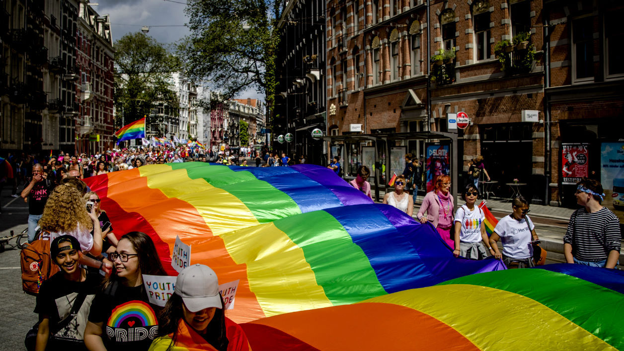 People hold a large rainbow flag during the Pride Walk through the center of Amsterdam on July 29, 2017. The march marks the beginning of Pride Amsterdam, a festival to raise awareness of LGBT rights. Sander Koning / ANP / AFP