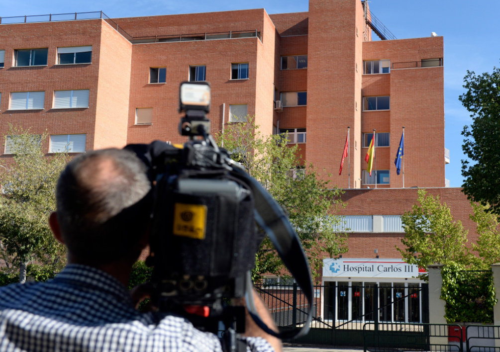 SPAIN, Madrid : A cameraman films the entrance to the Carlos III hospital before the arrival of Roman Catholic priest Miguel Pajares, who contracted the deadly Ebola virus, in Madrid on August 7, 2014. An elderly Spanish missionary infected with the deadly Ebola virus in Liberia landed in Madrid today, the first patient in the fast-spreading outbreak to be evacuated to Europe for treatment. AFP PHOTO / GERARD JULIEN