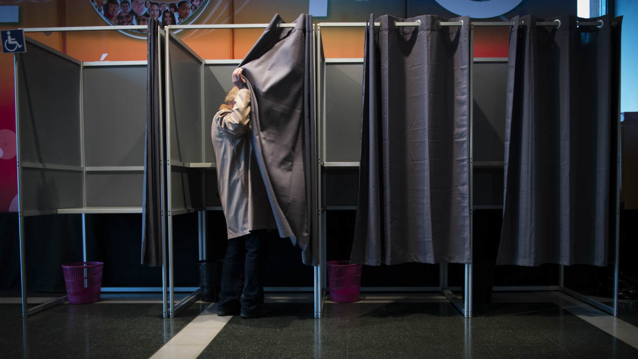A man gets into a voting booth on March 29, 2015 before voting in the second round of the French departemental elections at the Evry City Hall, south of Paris. AFP PHOTO MARTIN BUREAU
