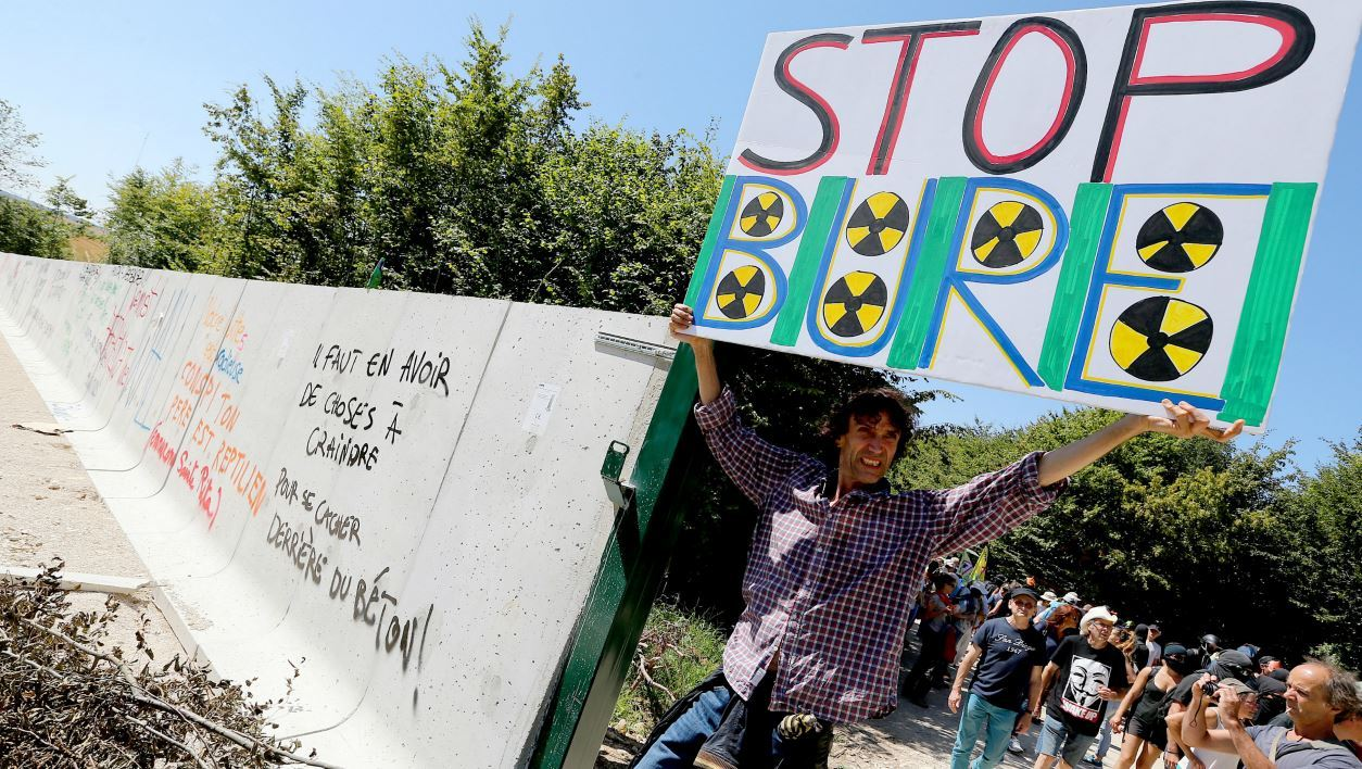 "Jean-Baptiste Redde aka Voltuan holds a placard reading ""Stop Bure"" as he stands by a wall erected by the French National Radioactive Waste Management Agency (ANDRA) to protect the area of the construction site for the creation of a radioactive waste storage during a protest against the project on August 14, 2016, in Bure."