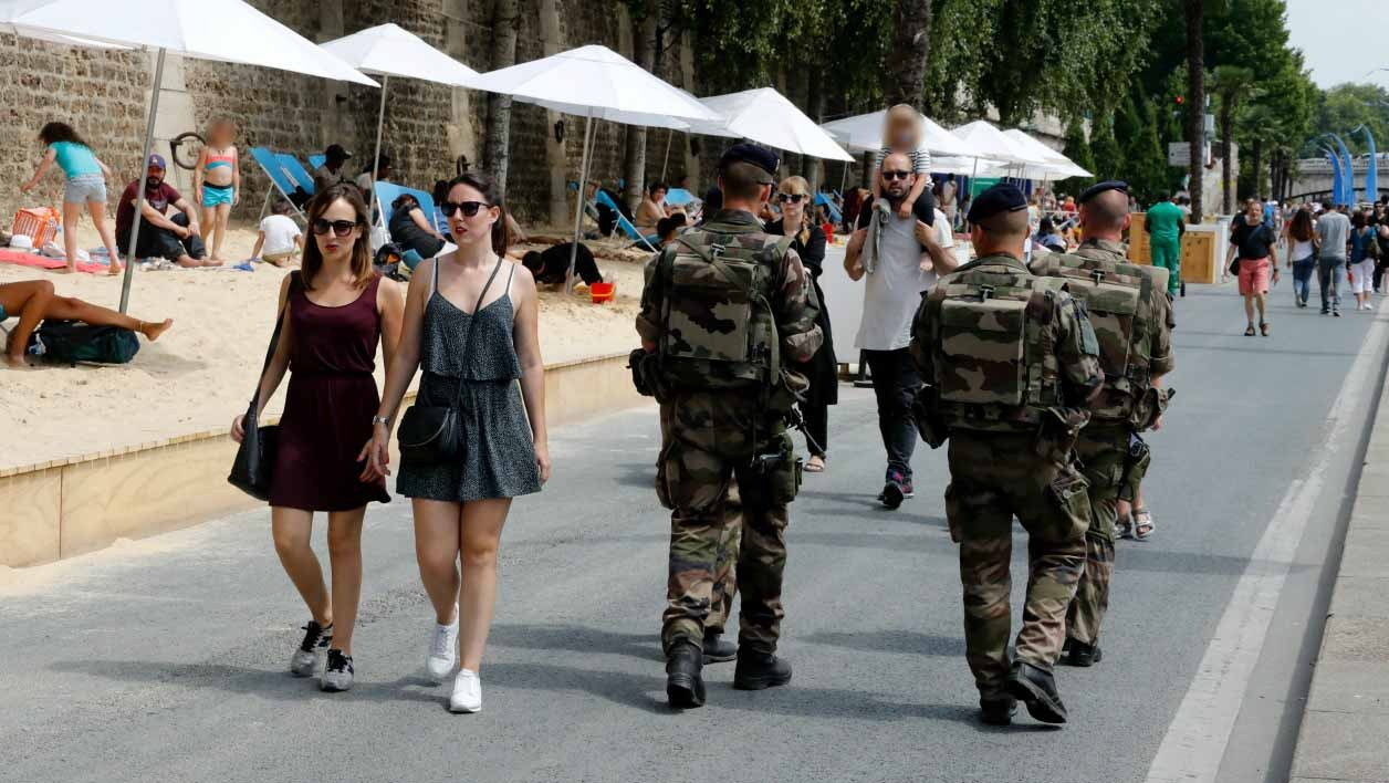 """French soldiers of Operation Sentinelle, patrol in """"Paris Plages"""" (Paris Beach) on the bank of the Seine river, in central Paris, on July 22, 2016.  FRANCOIS GUILLOT / AFP"""