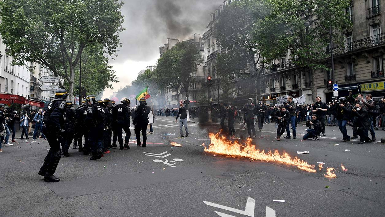 Riot police stand next to a fire during a protest against the government's labour reform on May 12, 2016 in Paris. France's already unpopular Socialist government faces a no-confidence vote on May 12, 2016 after it bypassed parliament and forced through a labour reform bill that has led to two months of demonstrations. Unions have called for more demonstrations on the same day to coincide with the vote of no confidence. AFP PHOTO / PHILIPPE LOPEZ