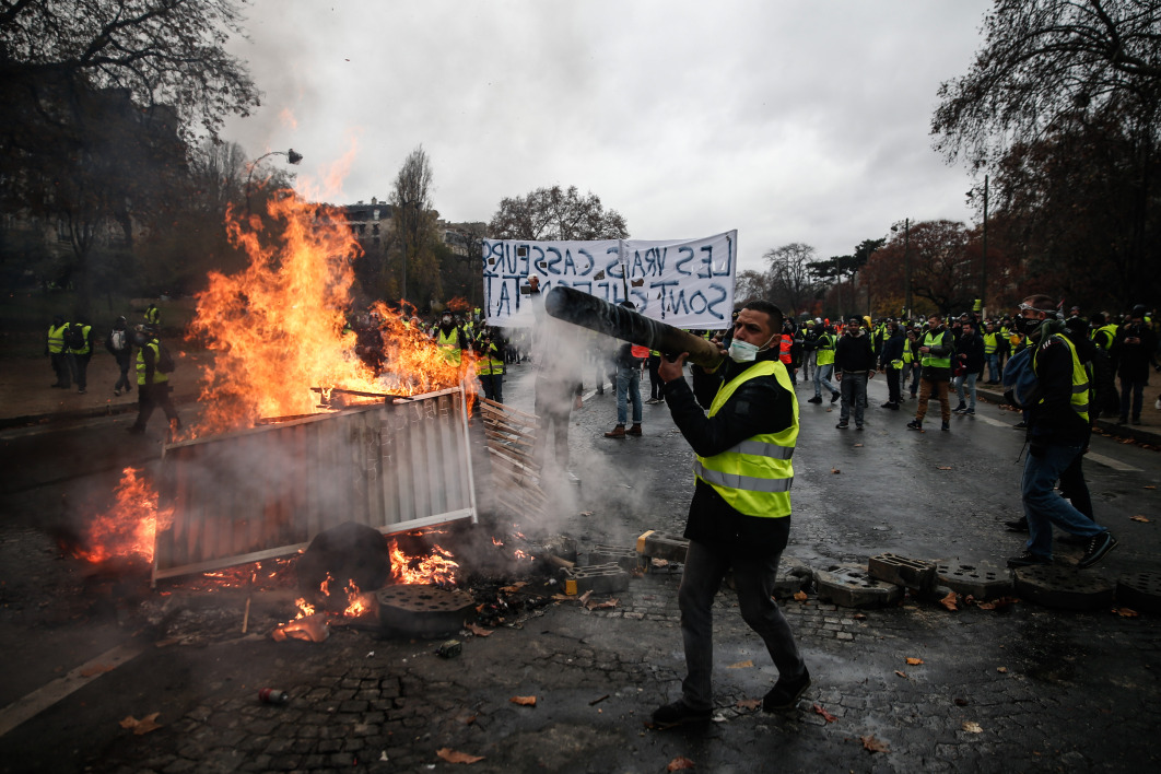Protesters build a barricade during a protest of Yellow vests (Gilets jaunes) against rising oil prices and living costs, on December 1, 2018 in Paris.  Abdulmonam EASSA / AFP