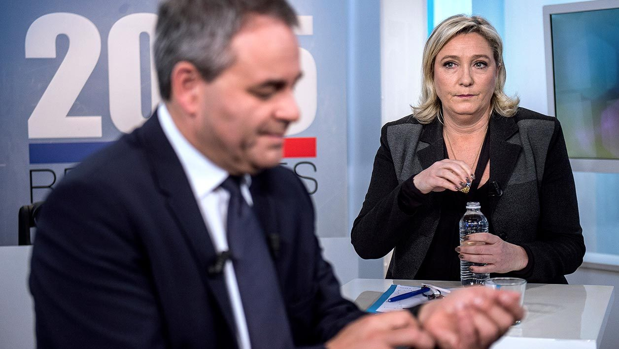 Candidates for the upcoming French regional elections in the Nord-Pas-de-Calais region, Xavier Bertrand (L) of the right-wing opposition Les Republicains (LR) party and Marine Le Pen (R), president of the far-right Front National (FN) party, sit and stand prior to a televised debate with other candidates in the region on December 3, 2015 on a set in the studios of French TV channel France 3 in Lille, northern France.