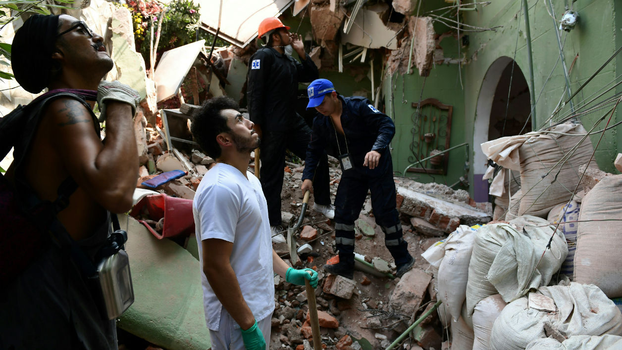 People remove debris of a collapsed building after a quake rattled Mexico City on September 19, 2017.