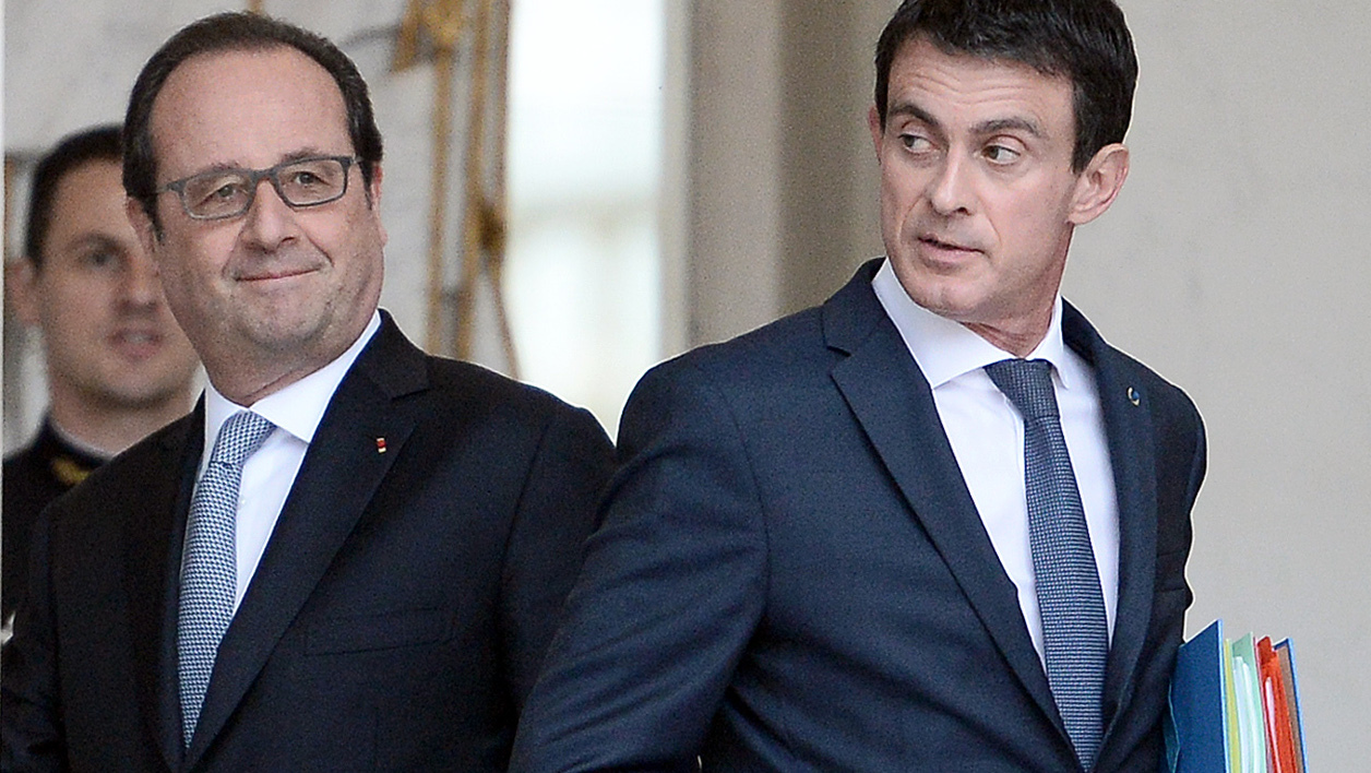 French President Francois Hollande (L) looks on as French Prime Minister Manuel Valls leaves after a weekly cabinet meeting on June 30, 2016 at the Elysee presidential Palace in Paris.  STEPHANE DE SAKUTIN / AFP