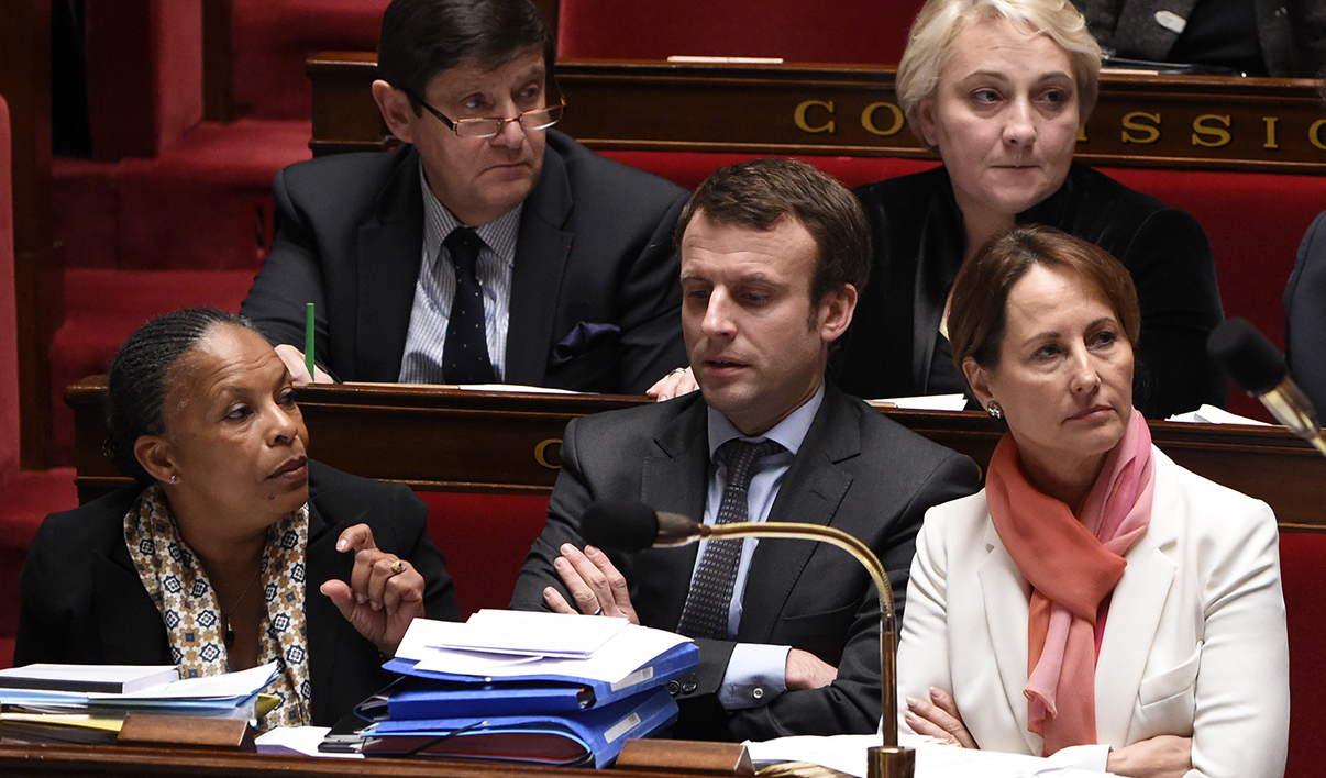 French Economy minister Emmanuel Macron (C) and Ecology minister Segolene Royal (R) speak with Justice minister Christiane Taubira during a session of Questions to the Government, on January 13, 2016 at the French National Assembly in Paris