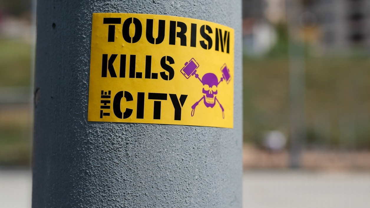 An anti-tourism sticker is pictured near Park Guell at the Vallcarca neighborhood on May 13, 2017 in Barcelona. PAU BARRENA / AFP