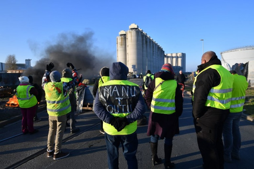 Yellow Vests (Gilets jaunes) take part in a road blockade on the third day of a movement against high fuel prices which has mushroomed into a widespread protest against stagnant spending power under French President on November 19, 2018 near the oil depot of La Rochelle, southwestern France.  XAVIER LEOTY / AFP
