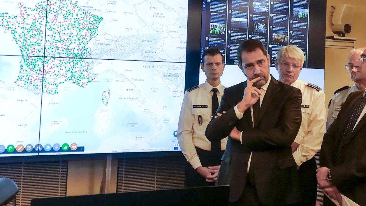 """French Interior Minister Christophe Castaner (2L) flanked by French Junior Minister attached to the Interior Ministry Laurent Nunez (R) gesture next to a map of France in the """"situation room"""" at the Interior Minister in Paris on November 17, 2018 during a national demonstration of Yellow Vests movement (Gilets jaunes) against the rising of the fuel and oil prices. French drivers seething over high fuel prices have vowed to snarl traffic across the country on November 17 in a widely"""