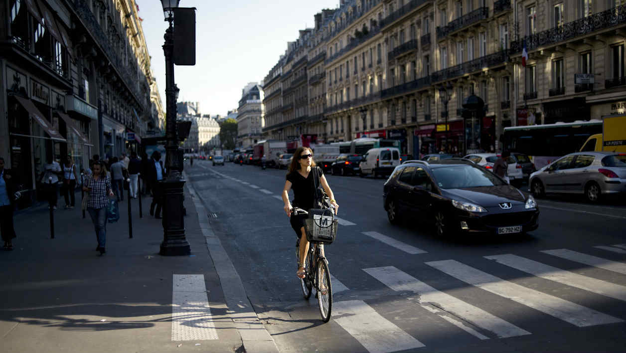 A woman rides a bike on the Avenue de l'Opera on September 29, 2011 in Paris. AFP PHOTO / FRED DUFOUR