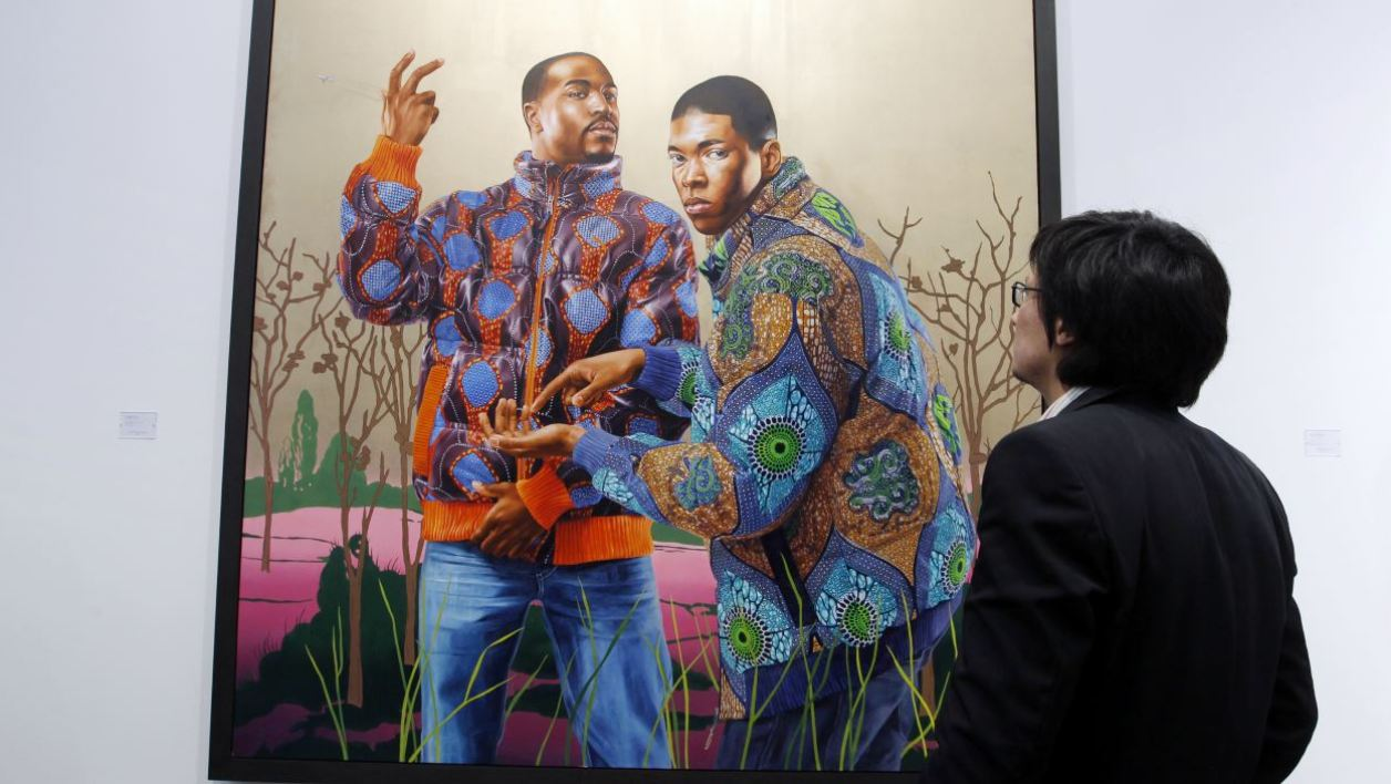"""A visitor looks at a piece titled """"Le paiement du tribut"""" by US artist Kehinde Wiley on the opening day of the International Contemporary Art Fair (FIAC) on October 19, 2011 at the Grand Palais in Paris. The 2011 edition, which runs from October 20 to 23, 2011 at the Grand Palais and the Louvre museum, features 168 exhibiting galleries and works from over 2,800 contemporary artists. AFP PHOTO / FRANCOIS GUILLOT FRANCOIS GUILLOT / AFP"""