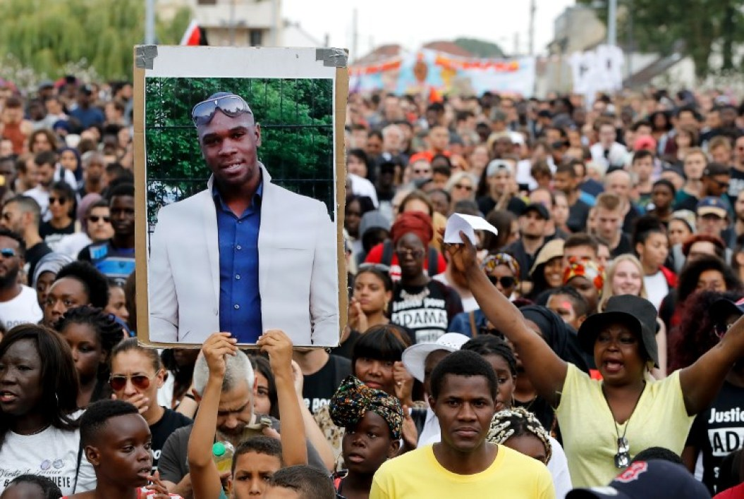 A person holds a portrait of late Adama Traore during a march calling for answers two years after the 24-year-old man died in police custody, on July 21, 2018 in Beaumont-sur-Oise, northeast of Paris. On July 19, 2016 Adama Traore, 24, died shortly after being arrested in the town of Beaumont-sur-Oise. Traore became a symbol and his family continues to call for truth and justice