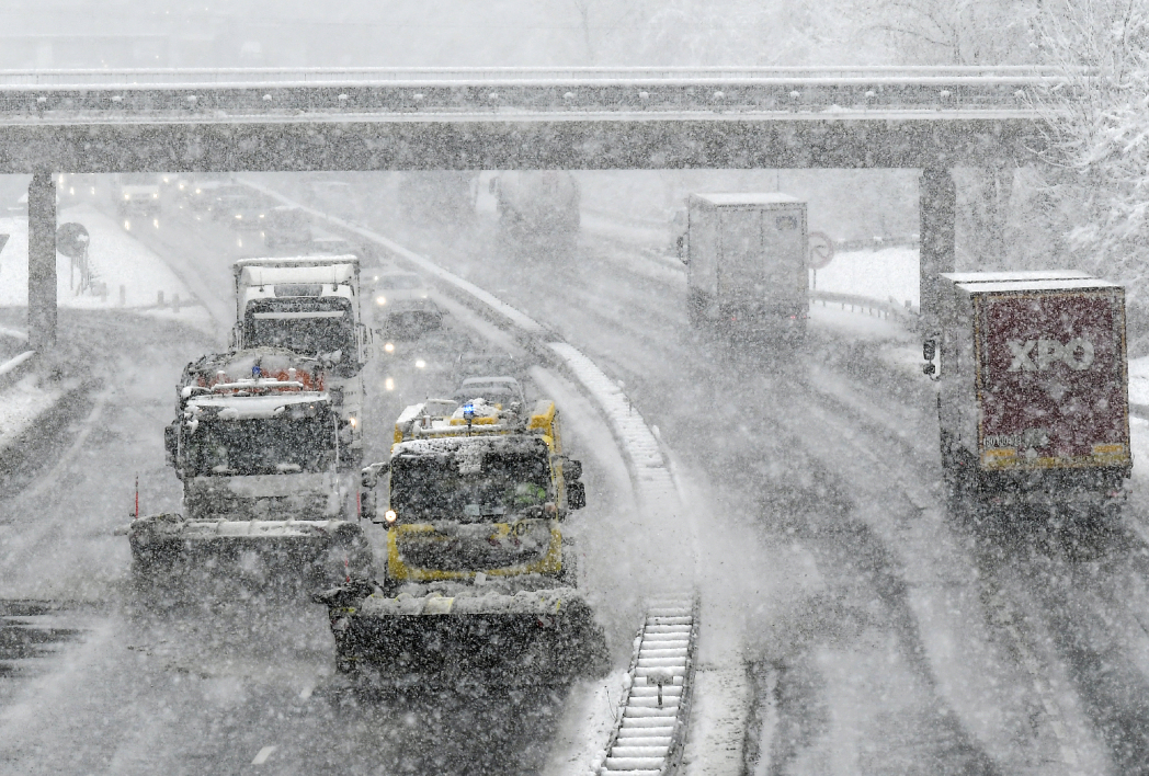A picture taken on December 1, 2017 shows a snowplough clearing the A43 highway between Lyon and Chambery due to heavy snow fall.  PHILIPPE DESMAZES / AFP