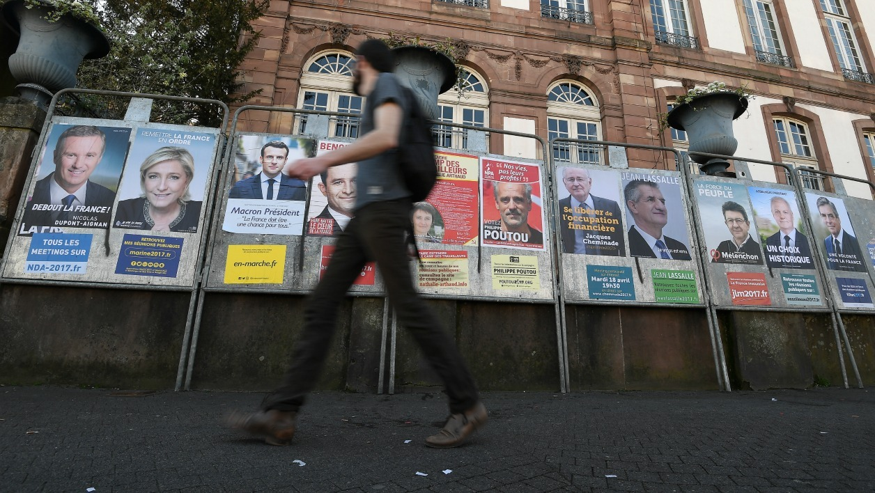 A person walks past campaign posters of the 11 candidates for the French presidential election on April 10, 2017 in Strasbourg, eastern France. The first round of the French presidential election will take place on April 23. FREDERICK FLORIN / AFP