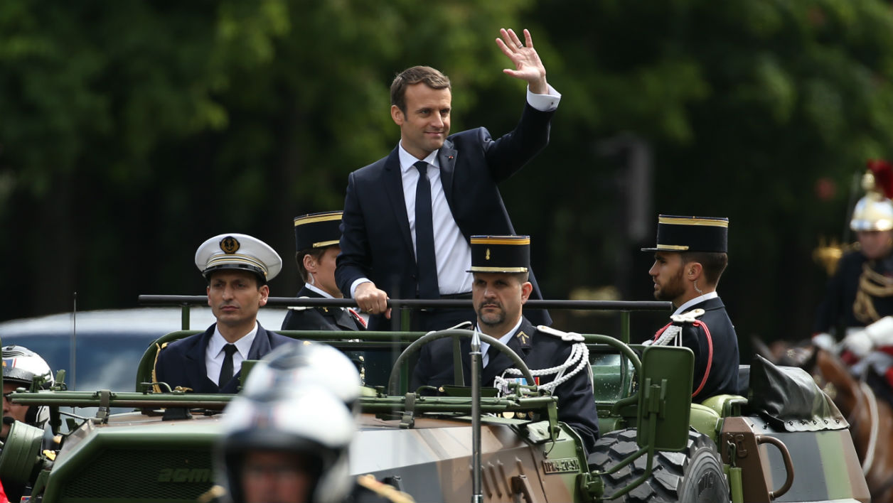 French President Emmanuel Macron waves as he parades in a car on the Champs Elysees avenue after his formal inauguration ceremony as French President on May 14, 2017 in Paris.  CHARLY TRIBALLEAU / AFP