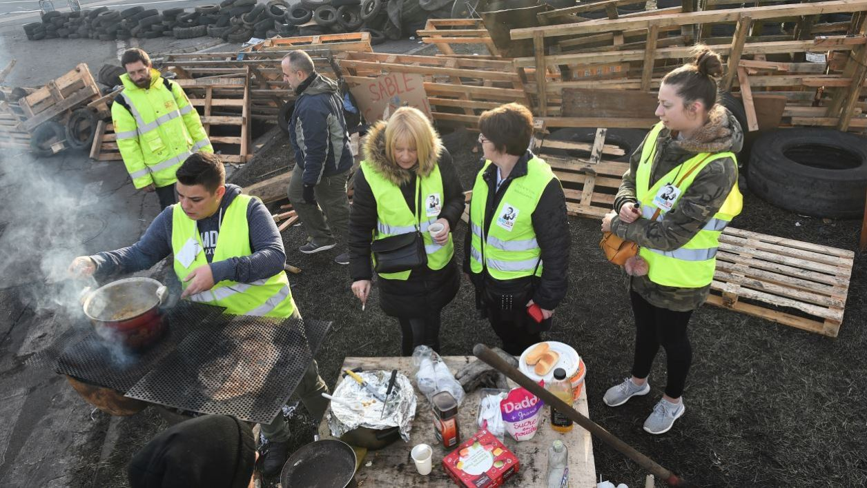 """""""Yellow vest"""" (gilets jaunes) protestors cook and talk together as they block the access to an oil depot in Le Mans, northwestern France, on December 10, 2018.  JEAN-FRANCOIS MONIER / AFP"""