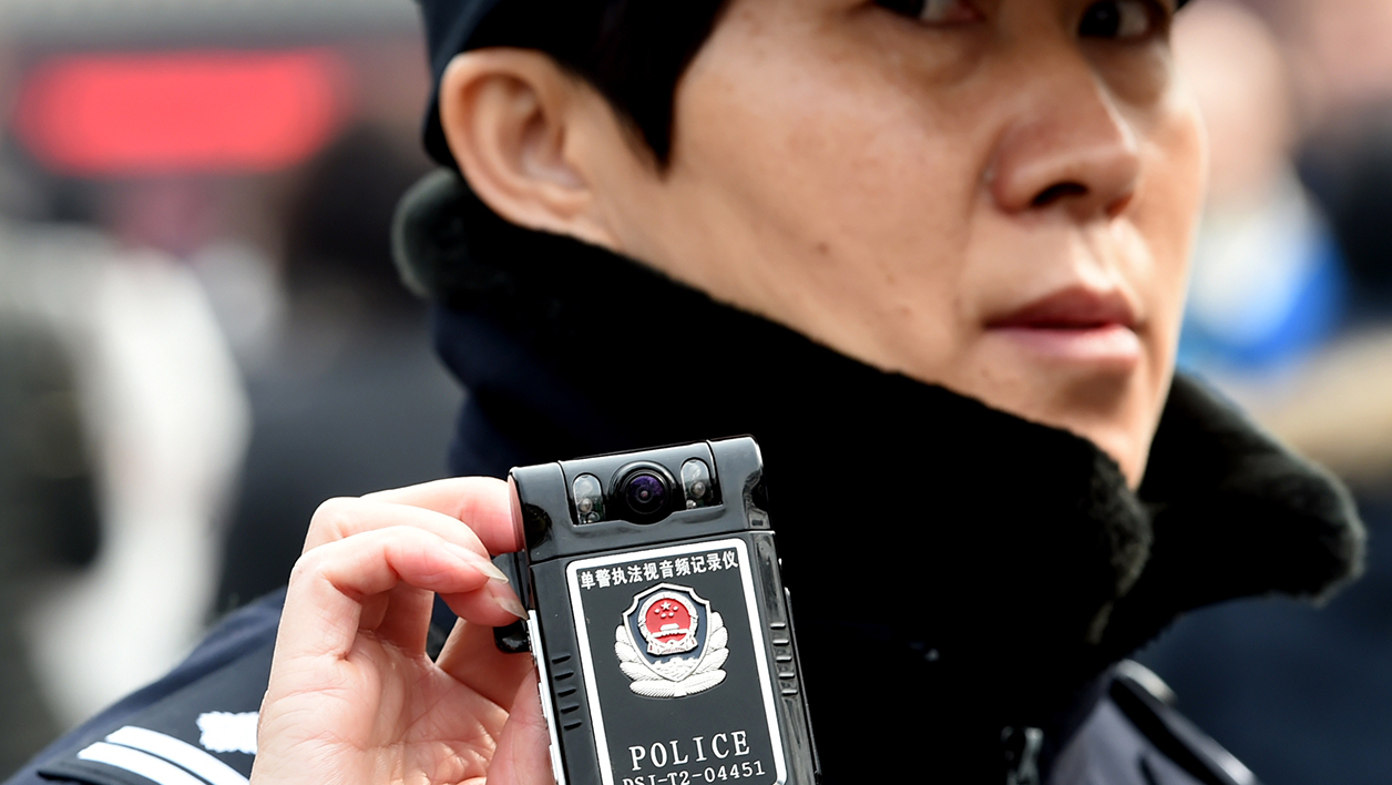 A police officer uses a pocket camera to record the foreign media covering the family members of Chinese passengers from the missing Malaysia Airlines flight MH370, at the Yonghegong Lama temple in Beijing on March 8, 2015. A year on, there remains no evidence to indicate what caused Malaysia Airlines Flight MH370 to vanish or where it ended up, despite the most expensive search operation in history.