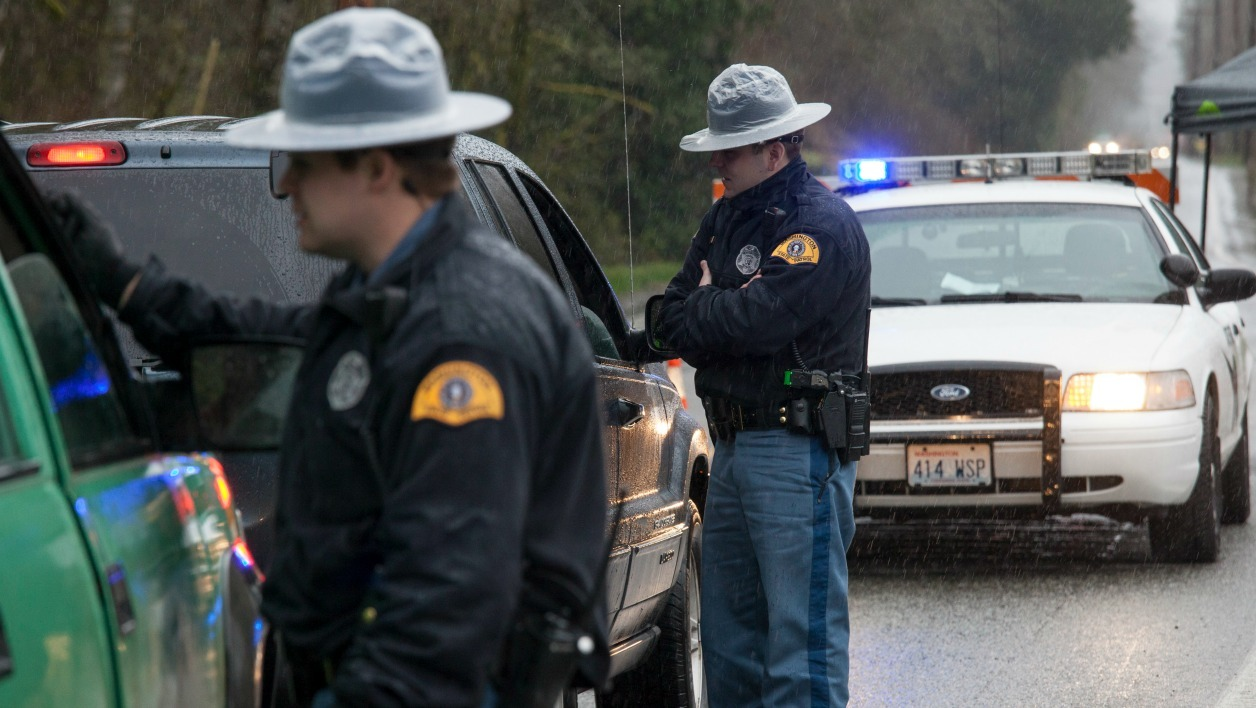 DARRINGTON, WA - MARCH 28: Washington State Patrol troopers stop vehicles at a road block on Washington Highway 530 near a massive mudslide on March 28, 2014 in Darrington, Washington. The mudslide on March 22 in nearby Oso, Washington killed at least 25 people and left many missing. David Ryder/Getty Images/AFP