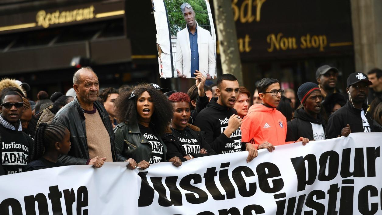 The elder sister (3rdL) of late Adama Traore (picture held up), and protesters take part in a march in Paris on November 5, 2016, to claim justice following the death of 24-year-old Adama Traore, who died during his arrest by the police in July 2016 in Beaumont-sur-Oise.  CHRISTOPHE ARCHAMBAULT / AFP