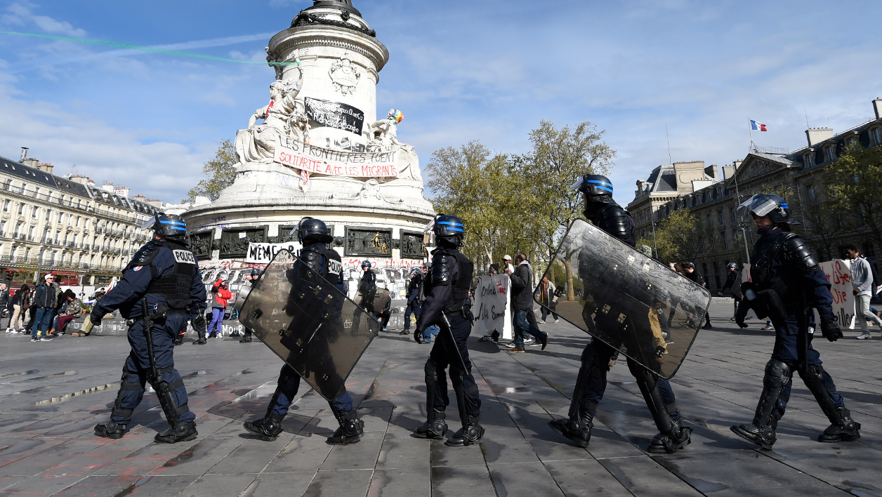 French CRS anti-riot police walk alongside protesters, including migrants who have occupied a high school in Paris' nineteenth district, as they walk through Place de la Republique in Paris on April 29, 2016 during a demonstration to call for better living conditions. The Regional Council has appealed to the administrative court which will consider on April 29 its request for the immediate evacuation of the migrants from the Jean Jaures high school in the nineteenth arrondissement of Paris. The high school, currently under renovation works, has been occupied by some 150 migrants since the night of April 21-22, 2016.  MIGUEL MEDINA / AFP