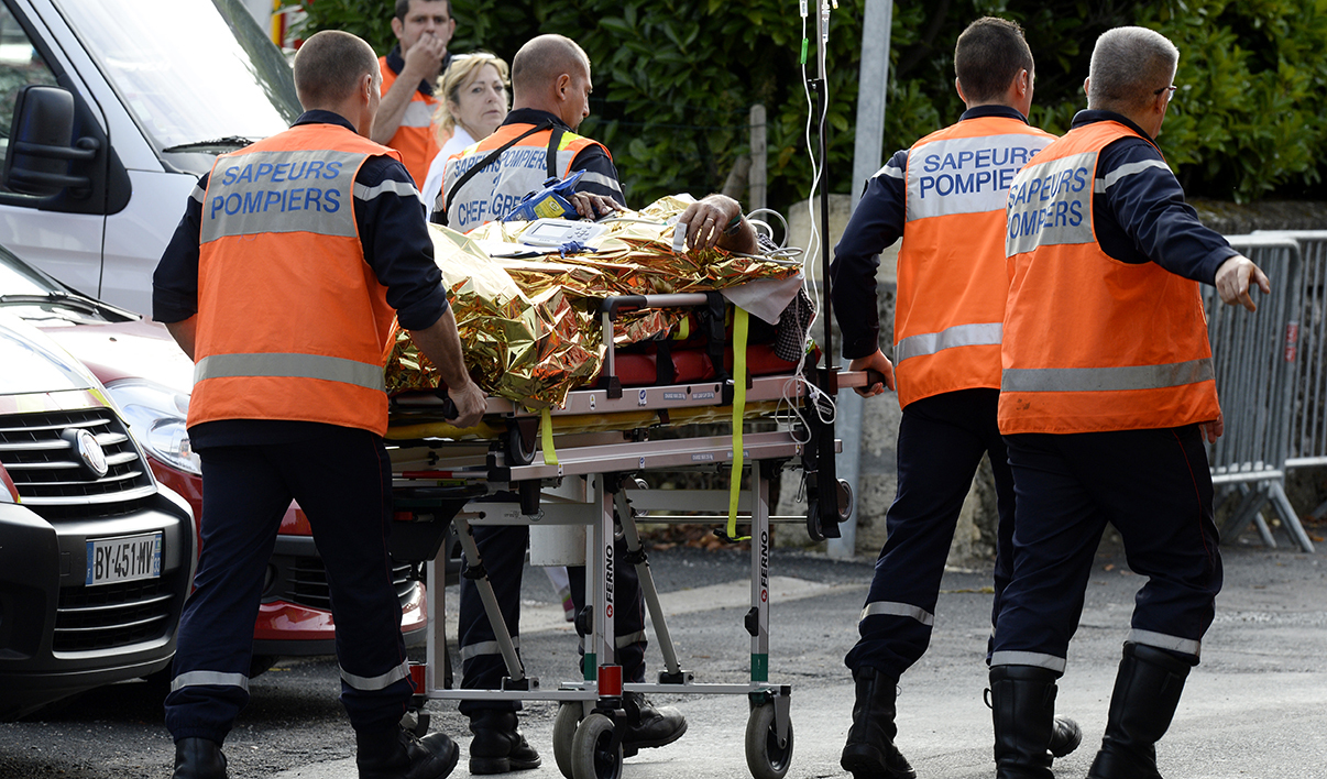 Emergency services personnel take away an injured person from the site of a collision on October 23, 2015 in Puisseguin, near Libourne, southwestern France. At least 42 people, most of them elderly, were killed when a coach collided with a lorry and caught fire in southwest France on October 23 in the country's worst road accident for three decades, officials said.