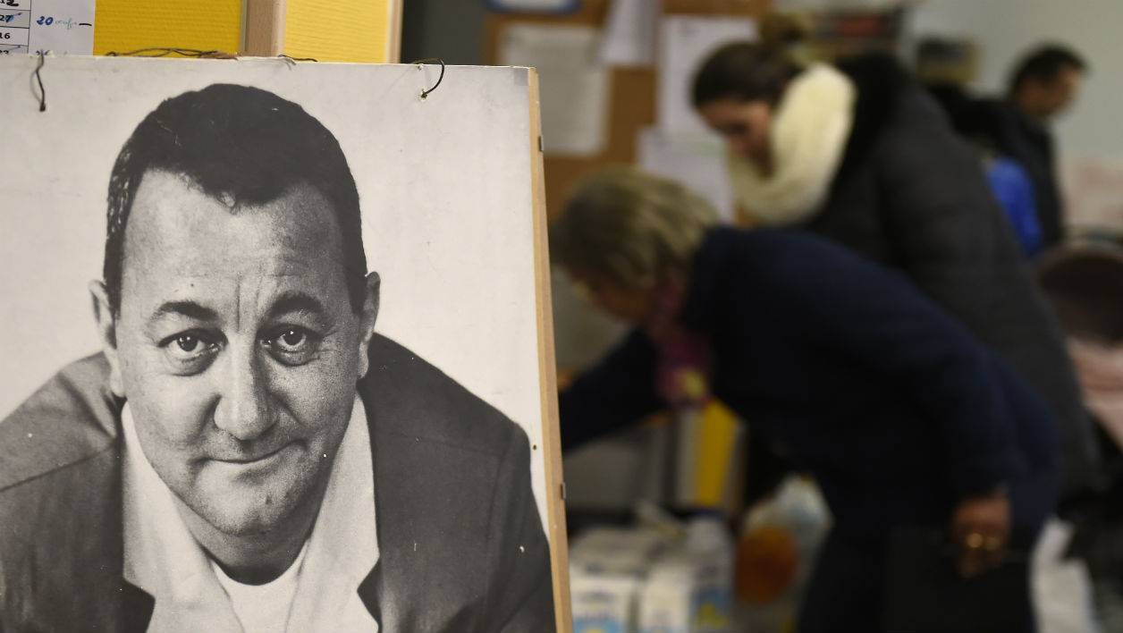"Volunteers of ""Les Restos du coeur"" French charity association distribute food to the needy person next to a portrait of French humorist and founder of ""Les Restos du coeur"" Coluche on December 1, 2015 in Lyon, southeastern France, as part of the association's 31th year of food distribution campaign."