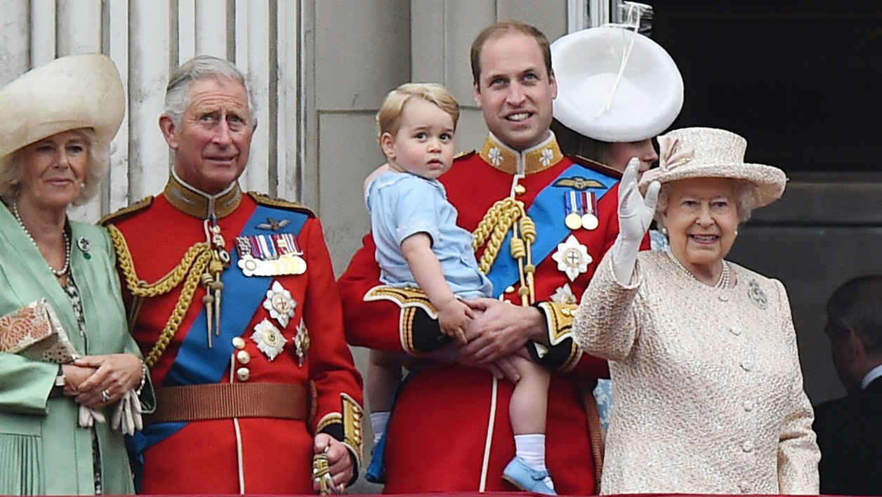 Britain's Queen Elizabeth II (R) waves from the balcony of Buckingham Palace with (L-R) Britain's Camilla, Duchess of Cornwall, Prince Charles, Prince of Wales, Prince William, Duke of Cambridge holding his son Prince George of Cambridge, and Catherine, Duchess of Cambridge (back) at the end of the Queen's Birthday Parade, 'Trooping the Colour,' in London on June 13, 2015. The ceremony of Trooping the Colour is believed to have first been performed during the reign of King Charles II. In 1748, it was decided that the parade would be used to mark the official birthday of the Sovereign. More than 600 guardsmen and cavalry make up the parade, a celebration of the Sovereign's official birthday, although the Queen's actual birthday is on 21 April. AFP PHOTO / BEN STANSALL