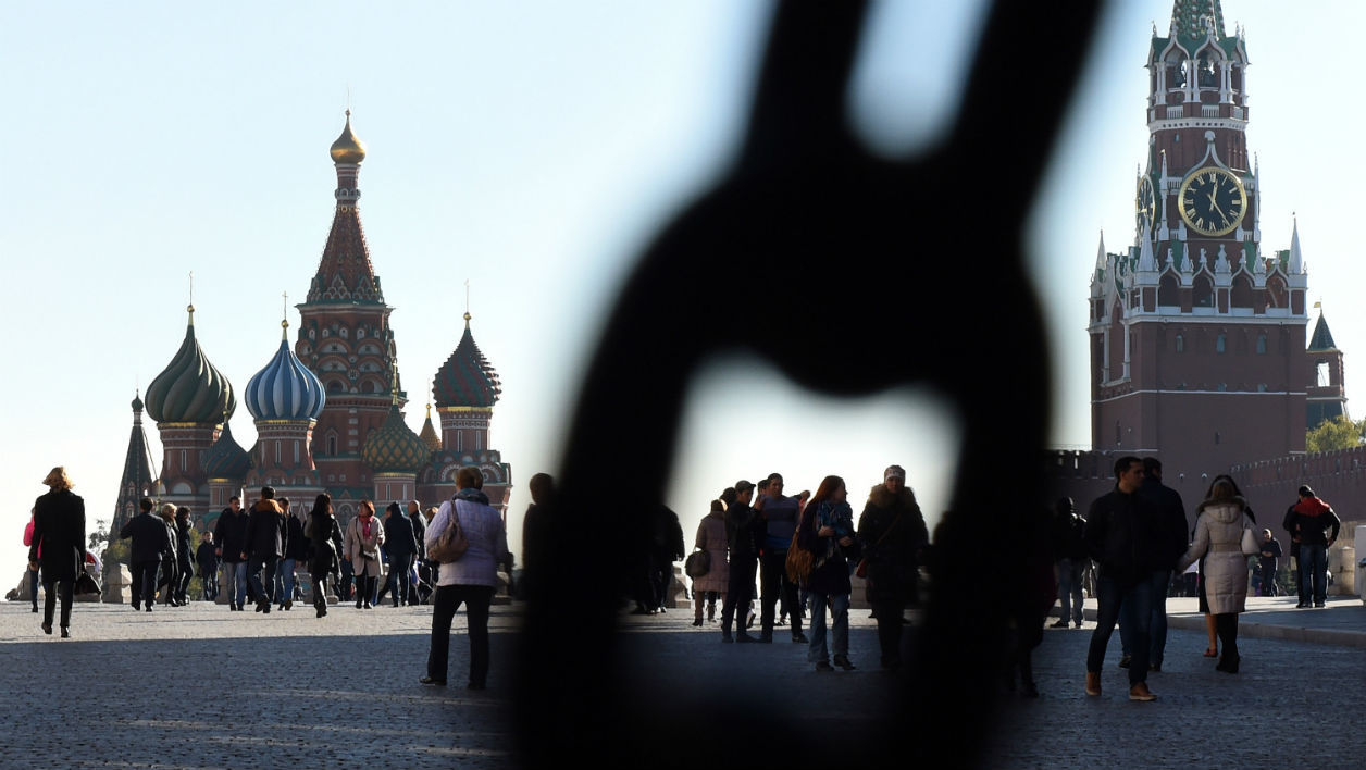 People walk across Red Square, with the Kremlin's Spasskaya (Saviour) Tower (right) and St. Basil's Cathedral (left) seen in the background, in central Moscow on October 16, 2015. AFP PHOTO / VASILY MAXIMOV  VASILY MAXIMOV / AFP