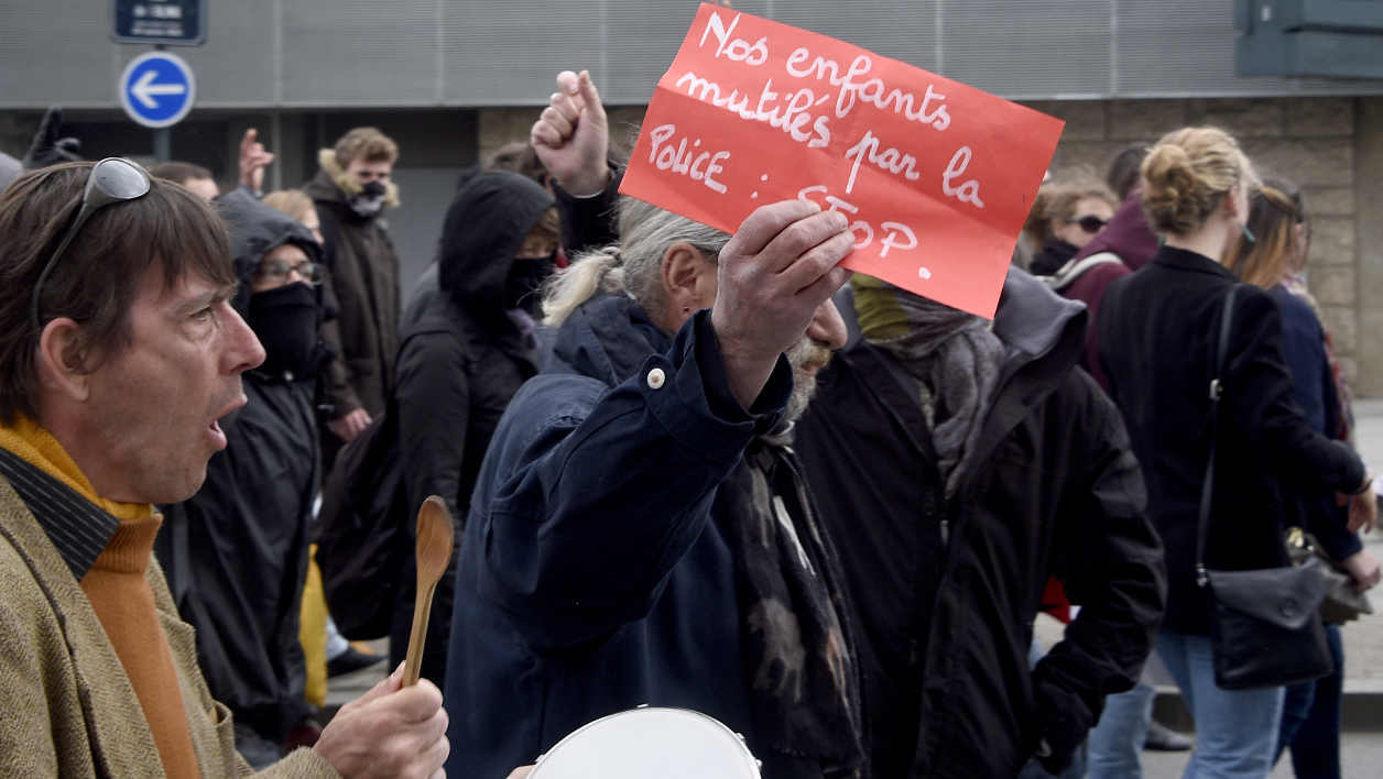 "A protester holds a placard reading ""Our children mutilated by the police"" on May 14, 2016 in Rennes, western France, during a demonstration against the government's planned labour law reforms. France's embattled Socialist government survived a vote of no-confidence on May 12 over its decision to force a controversial labour reform bill though parliament.  DAMIEN MEYER / AFP"