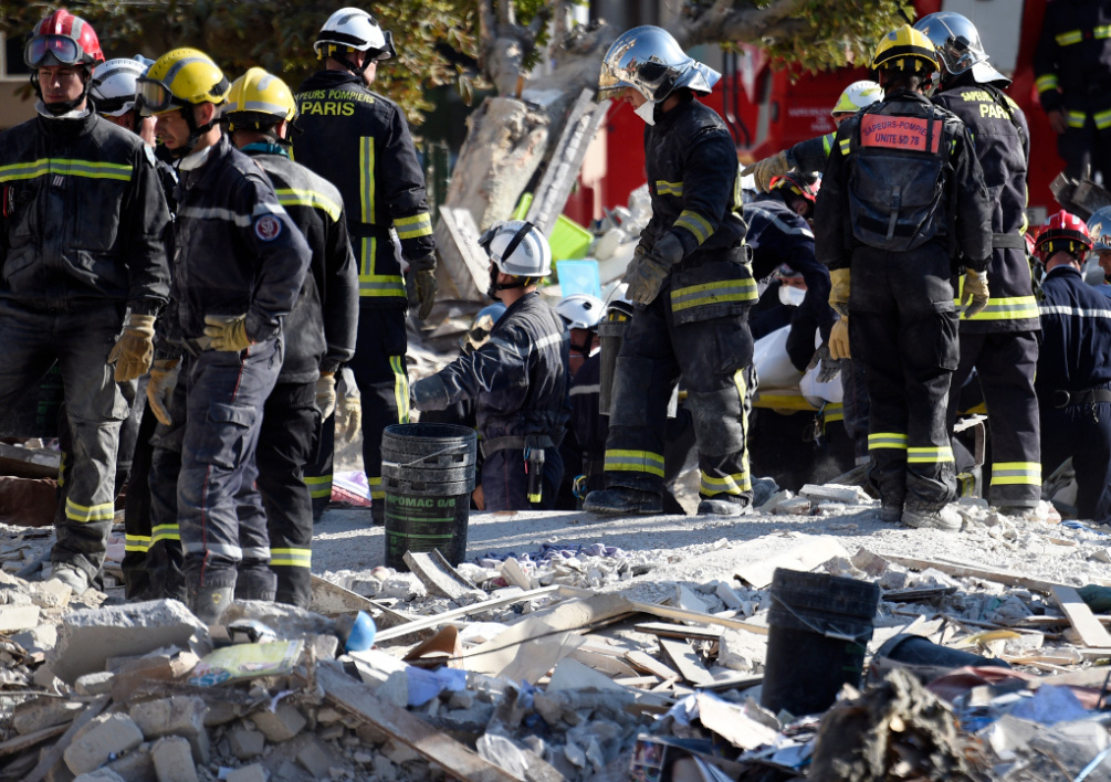 FRANCE, Rosny-sous-Bois : Firefighters search the rubble of a four-storey residential building which collapsed following a blast on September 01, 2014 in Rosny-sous-Bois in the eastern suburbs of Paris. A four-storey residential building collapsed in a Paris suburb following an explosion possibly due to a gas leak, killing at least seven people, local emergency services said. Eleven people were also wounded, including four in serious condition, while 11 others are still unaccounted for. AFP PHOTO / MARTIN BUREAU