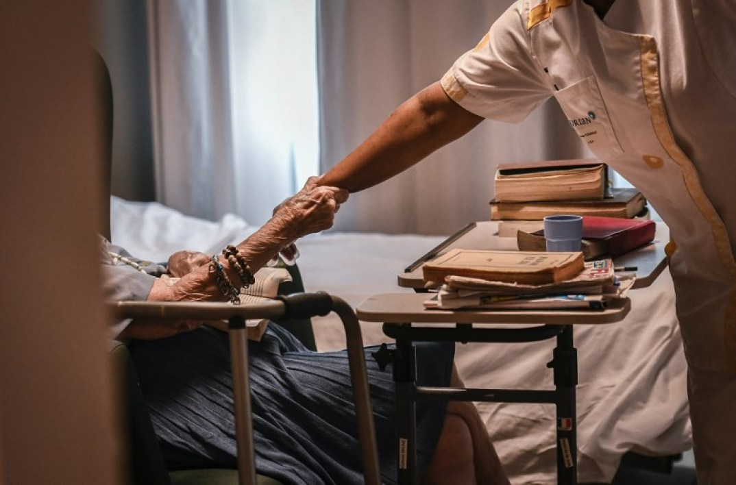 An elderly resident holds the forearm of a nurse on July 5, 2018, in an establishment of accommodation for dependent elderly (EHPAD) in Paris.  STEPHANE DE SAKUTIN / AFP
