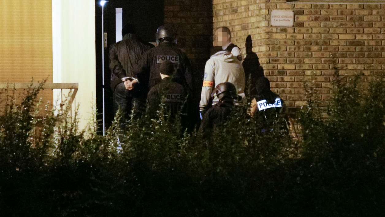 A handcuffed man is taken into a building in Boussy-Saint-Antoine south of Paris on September 8, 2016 where female suspects, said to have been planning new acts of violence, were arrested. French police investigating the discovery a car containing six gas cylinders in Paris, on Thursday arrested three female suspects said to have been planning new acts of violence, shooting one of them in the process. GEOFFROY VAN DER HASSELT / AFP