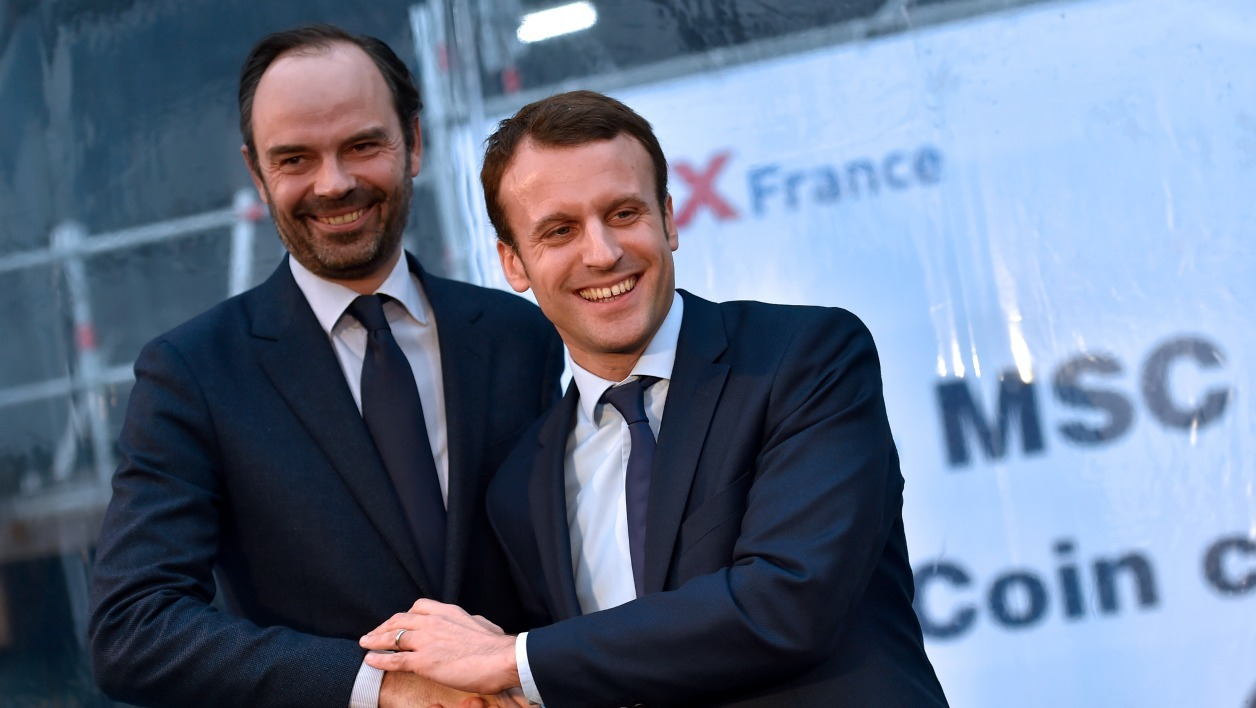French Economy Minister Emmanuel Macron (R) shakes hand with mayor of Le Havres Edouard Philippe during the MSC Meraviglia cruise ship coins ceremony at the STX shipyards, on February 1, 2016 in Saint-Nazaire, western France.  LOIC VENANCE / AFP