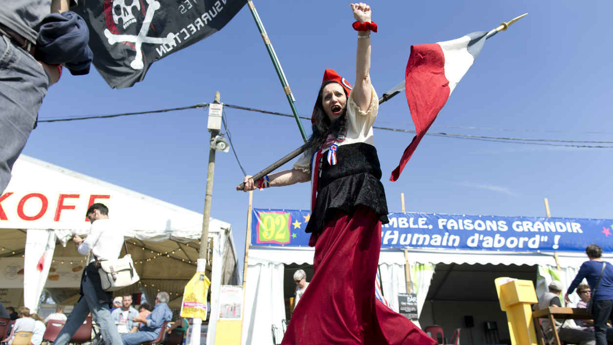 A woman wearing a Phrygian cap and dressed as a French 1789 revolutionary parades during the Festival of Humanity (Fete de l'Humanite), a political event and music festival organised by the French Communist party (PCF) on September 13, 2014 in La Courneuve, outside Paris. AFP PHOTO / KENZO TRIBOUILLARD