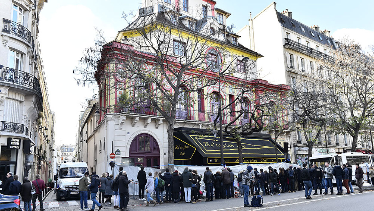 People gather in front of the Bataclan theatre in Paris, near a makeshift memorial for the victims of the attacks, on November 22, 2015.
