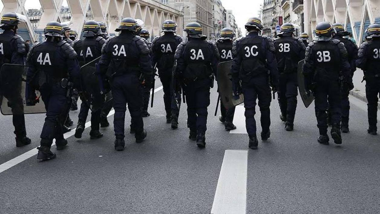 Riot policemen walk in the street during a demonstration against the labour reform laws in Paris on April 14, 2016. Young people have been at the forefront of mass demonstrations against the reforms over the past month, which the government argues are aimed at making France's rigid labour market more flexible.  THOMAS SAMSON / AFP