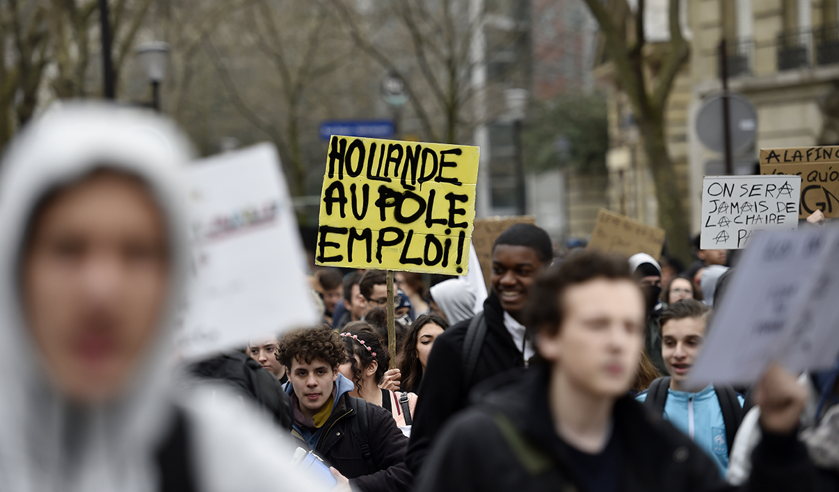 "A banner which translates as ""Hollande to the Job Centre"" is displayed as French youths and activists of various youth organisations march past during a demonstration against proposed changes to labour laws in Paris on March 24, 2016, during a day of action opposing the impementation of new labour legislation."